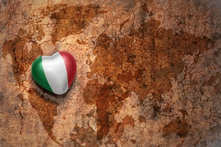 heart with national flag of italy on a vintage world map crack paper background. concept
