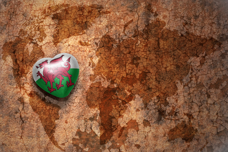 europe vintage: heart with national flag of wales on a vintage world map crack paper background. concept