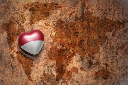 middle east peace: heart with national flag of indonesia on a vintage world map crack paper background. concept Stock Photo