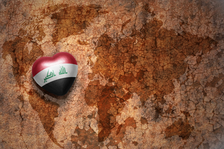 middle east peace: heart with national flag of iraq on a vintage world map crack paper background. concept