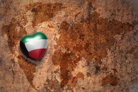 middle east peace: heart with national flag of kuwait on a vintage world map crack paper background. concept Stock Photo