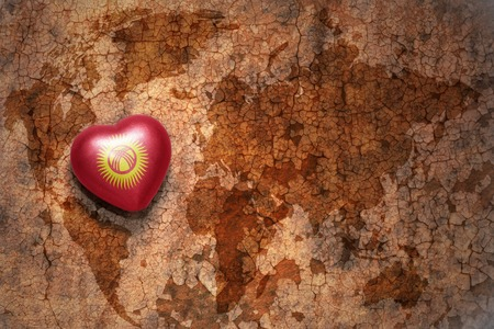 middle east peace: heart with national flag of kyrgyzstan on a vintage world map crack paper background. concept