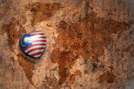 heart with national flag of malaysia on a vintage world map crack paper background. concept