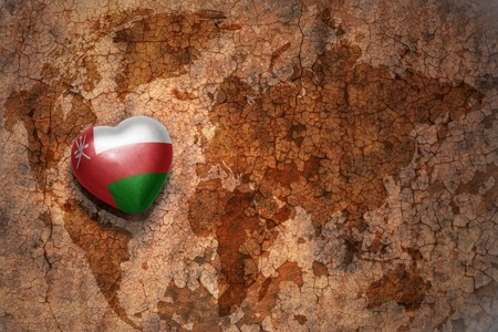 oman background: heart with national flag of oman on a vintage world map crack paper background. concept
