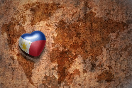 middle east peace: heart with national flag of philippines on a vintage world map crack paper background. concept