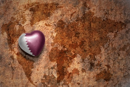 ancient near east: heart with national flag of qatar on a vintage world map crack paper background. concept