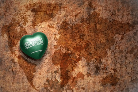 middle east peace: heart with national flag of saudi arabia on a vintage world map crack paper background. concept