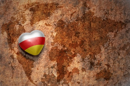 middle east peace: heart with national flag of south ossetia on a vintage world map crack paper background. concept