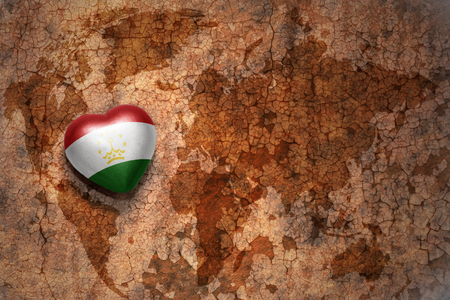 middle east peace: heart with national flag of tajikistan on a vintage world map crack paper background. concept