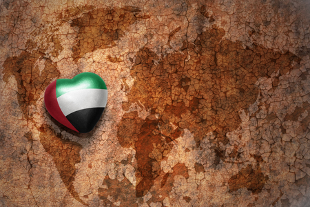 middle east peace: heart with national flag of united arab emirates on a vintage world map crack paper background. concept