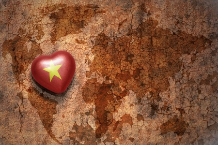 middle east peace: heart with national flag of vietnam on a vintage world map crack paper background. concept