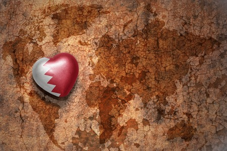 middle east peace: heart with national flag of bahrain on a vintage world map crack paper background. concept Stock Photo