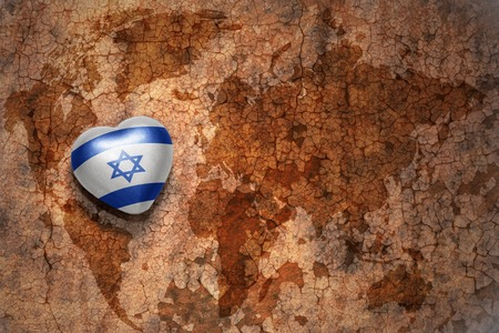 heart with national flag of israel on a vintage world map crack paper background. concept