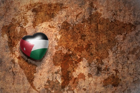 ancient near east: heart with national flag of jordan on a vintage world map crack paper background. concept