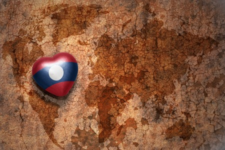 middle east peace: heart with national flag of laos on a vintage world map crack paper background. concept