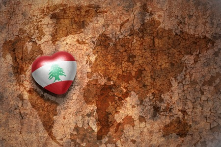 middle east peace: heart with national flag of lebanon on a vintage world map crack paper background. concept