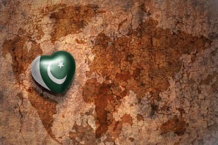 middle east peace: heart with national flag of pakistan on a vintage world map crack paper background. concept