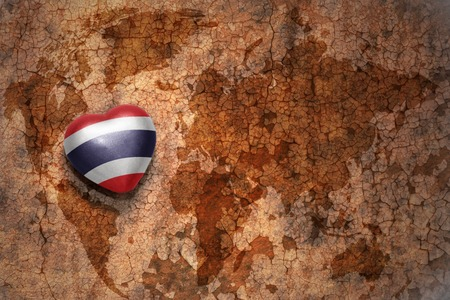 middle east peace: heart with national flag of thailand on a vintage world map crack paper background. concept