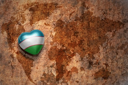 middle east peace: heart with national flag of uzbekistan on a vintage world map crack paper background. concept