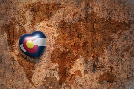 capital of colorado: heart with colorado state flag  on a vintage world map crack paper background. concept