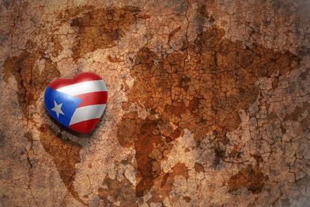 bandera de puerto rico: corazón con la bandera nacional de Puerto Rico en un mapa mundial de papel de fondo grieta de la vendimia. concepto