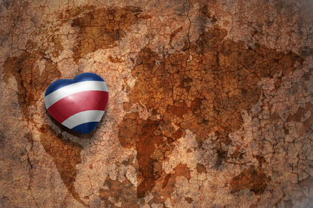 costa rican flag: heart with national flag of costa rica on a vintage world map crack paper background. concept