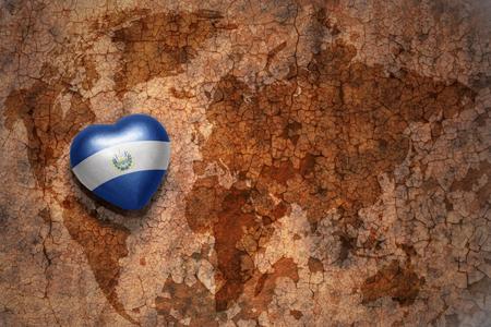 mapa de el salvador: coraz�n con la bandera nacional de El Salvador en un mapa mundial de papel de fondo grieta de la vendimia. concepto
