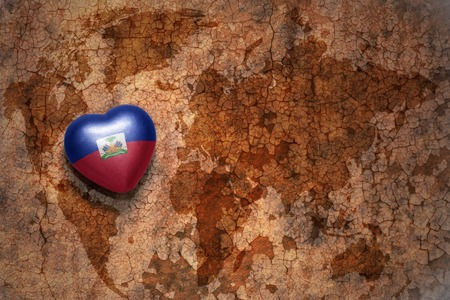 prince of peace: heart with national flag of haiti on a vintage world map crack paper background. concept Stock Photo