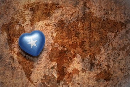 somali: heart with national flag of somalia on a vintage world map crack paper background. concept Stock Photo