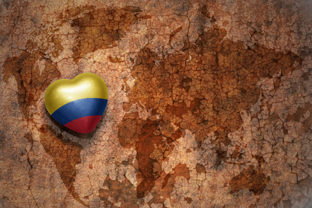 heart with national flag of colombia on a vintage world map crack paper background. concept