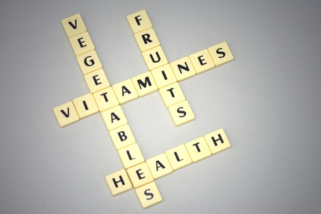 vitamines: words vegetables, fruits, health, and vitamines on a gray background. concept