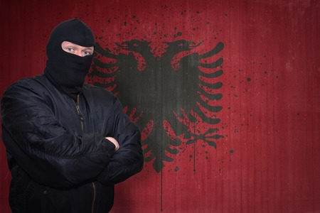 dangerous man: dangerous man in a mask standing near a wall with painted national flag of albania