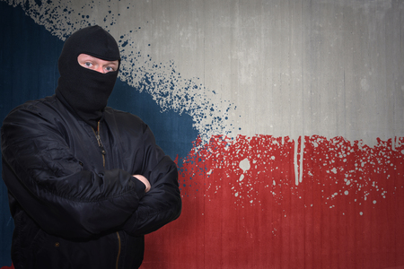 terrorism crisis: dangerous man in a mask standing near a wall with painted national flag of czech republic Stock Photo