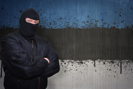 dangerous man: dangerous man in a mask standing near a wall with painted national flag of estonia Stock Photo