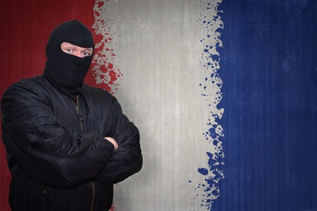 terrorism crisis: dangerous man in a mask standing near a wall with painted national flag of france