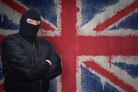 dangerous man: dangerous man in a mask standing near a wall with painted national flag of great britain Stock Photo