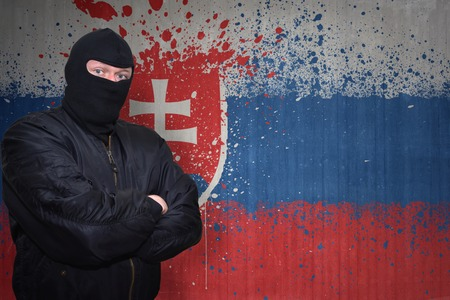 terrorism crisis: dangerous man in a mask standing near a wall with painted national flag of slovakia