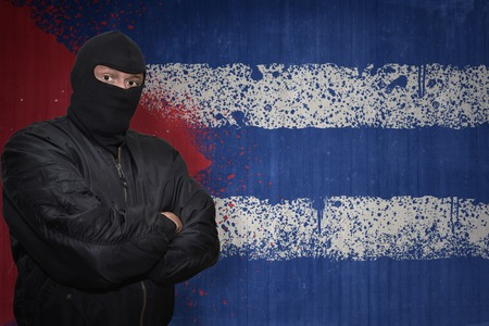 terrorism crisis: dangerous man in a mask standing near a wall with painted national flag of cuba