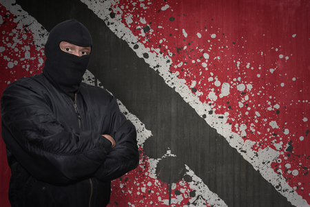 national flag trinidad and tobago: dangerous man in a mask standing near a wall with painted national flag of trinidad and tobago Stock Photo