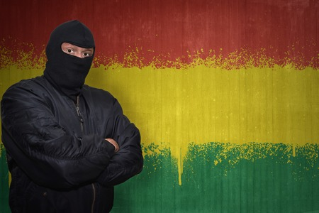 terrorism crisis: dangerous man in a mask standing near a wall with painted national flag of bolivia Stock Photo