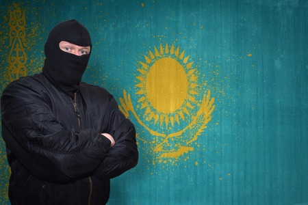 terrorism crisis: dangerous man in a mask standing near a wall with painted national flag of kazakhstan