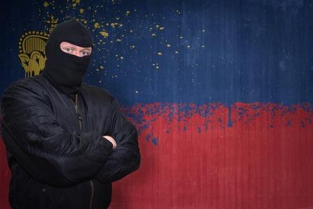 terrorism crisis: dangerous man in a mask standing near a wall with painted national flag of liechtenstein
