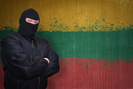 terrorism crisis: dangerous man in a mask standing near a wall with painted national flag of lithuania