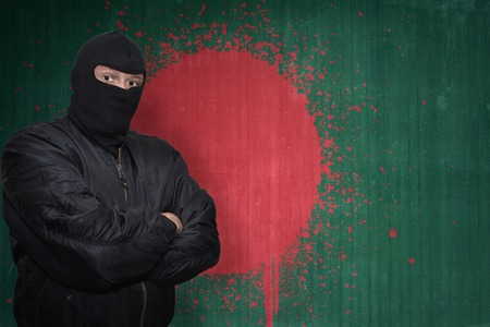 national flag bangladesh: dangerous man in a mask standing near a wall with painted national flag of bangladesh
