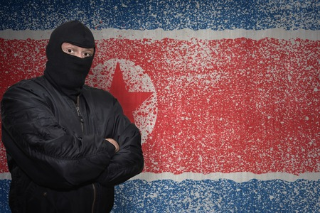 middle east conflict: dangerous man in a mask standing near a wall with painted national flag of north korea