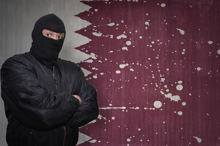 middle east crisis: dangerous man in a mask standing near a wall with painted national flag of qatar