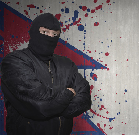 middle east crisis: dangerous man in a mask standing near a wall with painted national flag of nepal Stock Photo