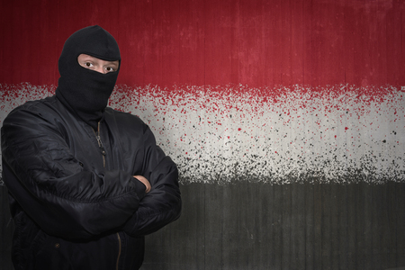 middle east conflict: dangerous man in a mask standing near a wall with painted national flag of yemen