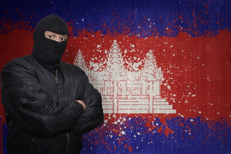 middle east crisis: dangerous man in a mask standing near a wall with painted national flag of cambodia