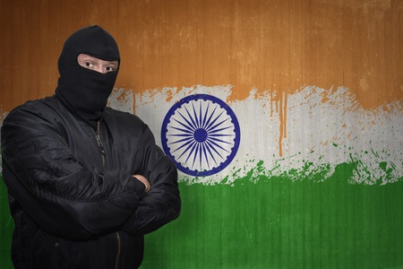 middle east crisis: dangerous man in a mask standing near a wall with painted national flag of india